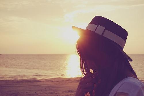 海で夕陽を浴びる女性の画像