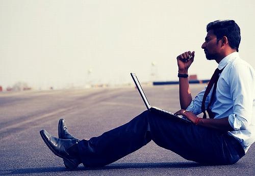 PCをもって外で仕事をしている男性