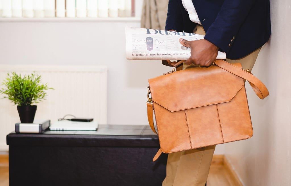 男性、ジャケットにパンツをはいて新聞とバッグを持っている画像