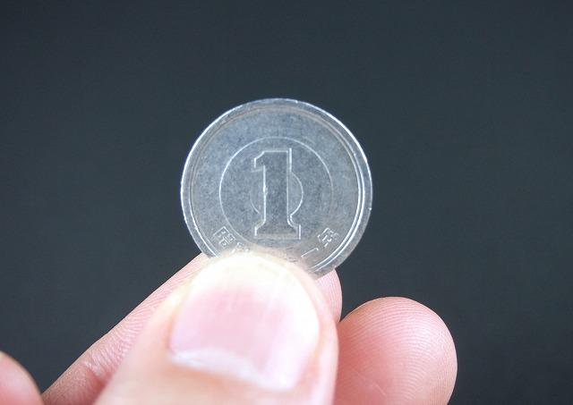 1円を持つ指の画像