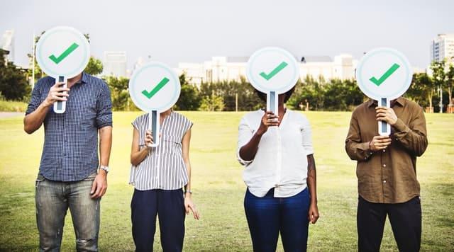 チェックマークを顔に当てている4人の人間の画像