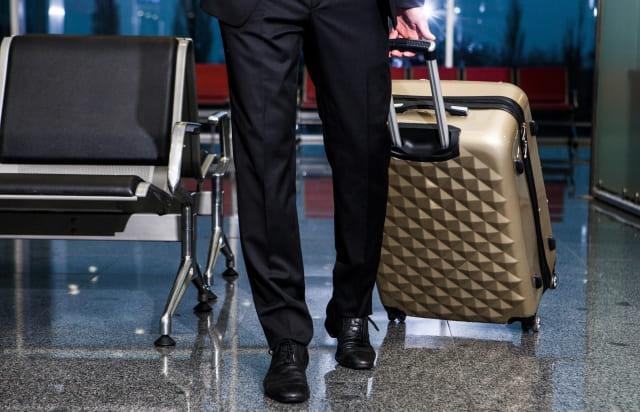ビジネスマンが空港でスーツケース引いてる画像